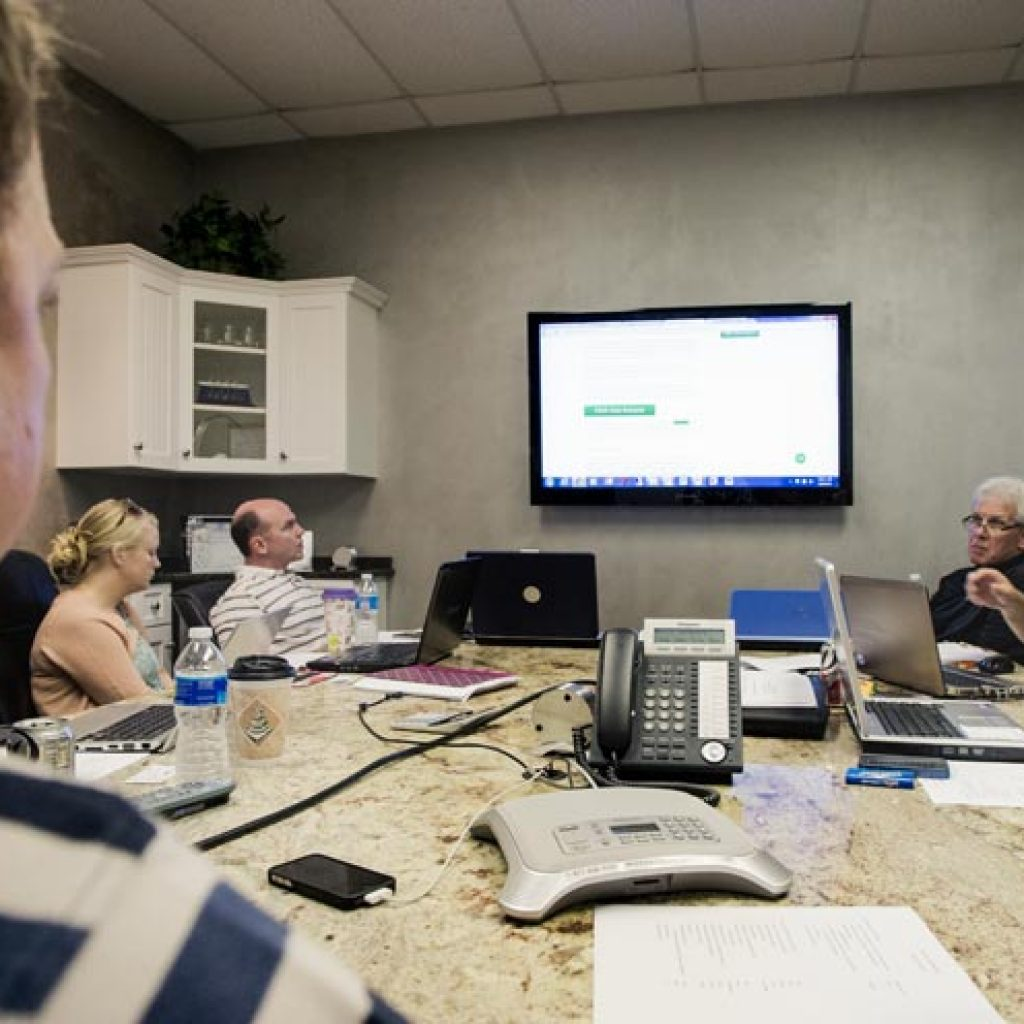 The TI team around a conference table looking at a screen on the wall.