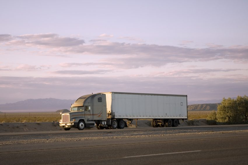 A truck on a road in front of plains with mountains in the distance.