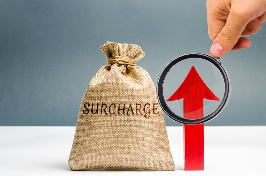 """A hand holding a magnifying glass looking at a red arrow which points up. Next to the red arrow is a burlap sack with the word """"Surcharge"""" on it."""